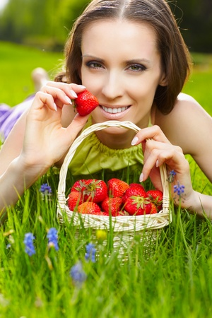 outdoor portrait of happy beautiful woman lying on grass with bunch of strawberry photo