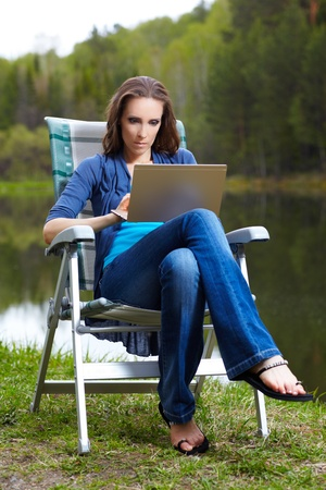 outdoor portrait of beautiful woman sitting in folding chair with laptop near the pond in forest photo