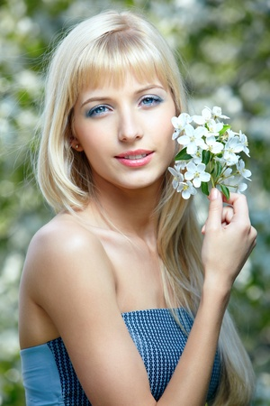 outdoor portrait of happy beautiful blue-eyed blonde girl posing with flowers in her hair Stock Photo - 9782217