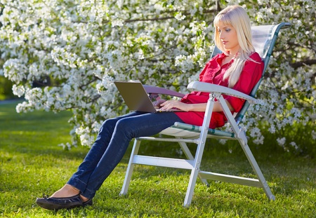 outdoor portrait of beautiful blonde girl sitting in folding chair on green grass near bloomin apple tree with laptop photo