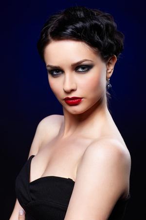 portrait of beautiful brunette girl posing on blue Stock Photo - 9970942