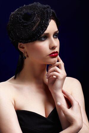 Retrato de muchacha hermosa morena posando en azul en el sombrero de encaje negro