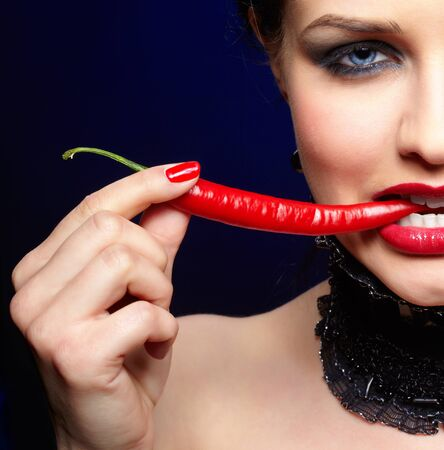 portrait of beautiful brunette girl in black lacy collar biting spicy hot red cayenne photo