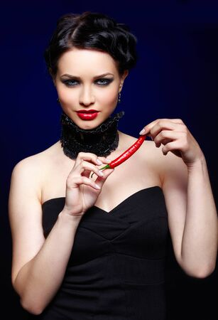 portrait of beautiful brunette girl in black lacy collar posing with spicy hot red cayenne photo