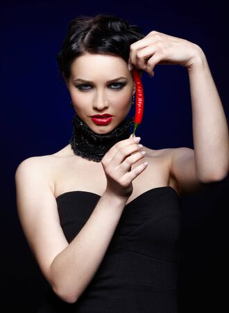 portrait of beautiful brunette girl in black lacy collar posing with spicy hot red cayenne Stock Photo - 9970938