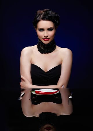 portrait of beautiful brunette girl posing with fork, knife and single red hot spicy cayenne on white plate photo