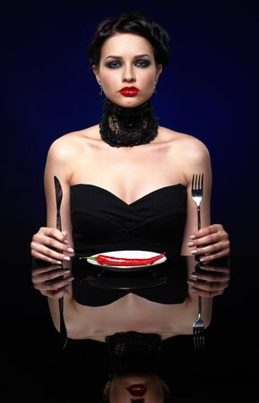 red taste: portrait of beautiful brunette girl posing with fork, knife and single red hot spicy cayenne on white plate Stock Photo