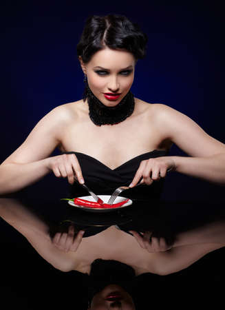 portrait of beautiful brunette girl cutting red hot spicy cayenne with fork and knife on white plate photo