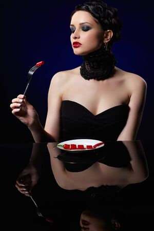 portrait of beautiful brunette girl posing with fork and single red hot spicy cayenne on white plate Stock Photo - 9970887