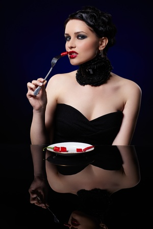 reducing: portrait of beautiful brunette girl posing with fork and single red hot spicy cayenne on white plate