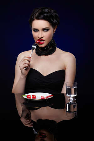 portrait of beautiful brunette girl posing with fork and single red hot spicy cayenne on white plate photo