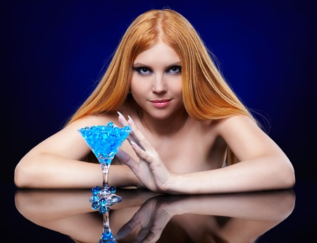 portrait of beautiful long-haired blue-eyed redhead girl with glass of fantasy cocktail photo