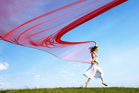 60s hippie: outdoor portrait of beautiful hippie girl running with big piece of red light cloth under the blue sky