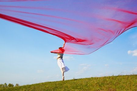 outdoor portrait of beautiful hippie girl running with big piece of red light cloth under the blue sky Stock Photo - 9971046