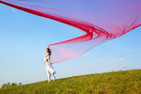 wind dress: outdoor portrait of beautiful hippie girl running with big piece of red light cloth under the blue sky