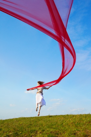outdoor portrait of beautiful hippie girl jumping with big piece of red light cloth under the blue sky photo