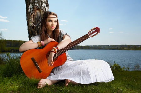 outdoor portrait of beautiful hippie girl sitting on green grass near birch with guitar. lake and forest on background Stock Photo