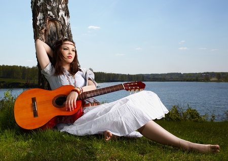 60s hippie: outdoor portrait of beautiful hippie girl sitting on green grass near birch with guitar. lake and forest on background Stock Photo