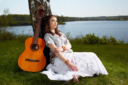 outdoor portrait of beautiful hippie girl sitting on green grass near birch with guitar. lake and forest on background photo