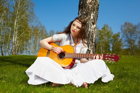 outdoor portrait of beautiful hippie girl sitting near birch on green grass with guitar photo