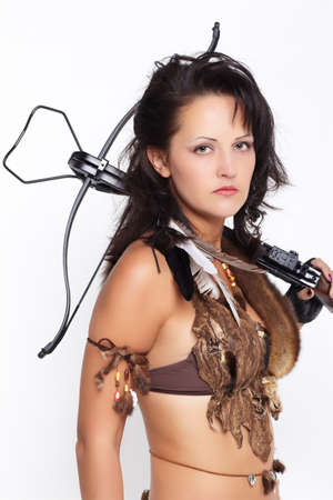 portrait of beautiful woman fur hunter with crossbow on gray photo