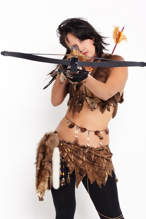 portrait of beautiful woman fur hunter with crossbow aiming at the camera photo