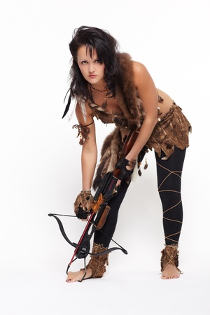 full-length portrait of beautiful woman fur hunter reloading crossbow on gray photo