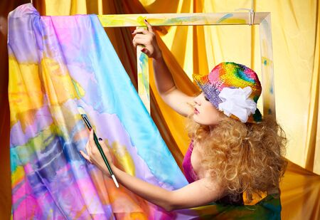 portrait of beautiful woman artist with paintbrush standing behind the easel with painted cloth on it photo