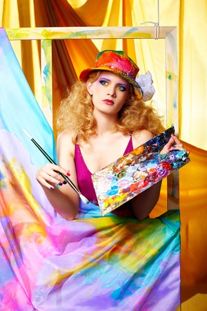 portrait of beautiful woman artist with paintbrush and palette standing behind the easel with painted cloth on it photo