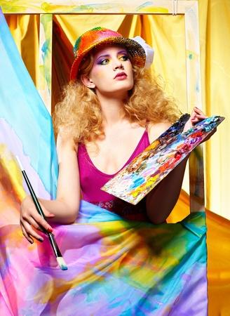 tavolozza pittore: ritratto di artista donna bellissima con pennello e tavolozza in piedi dietro il cavalletto con tela dipinta