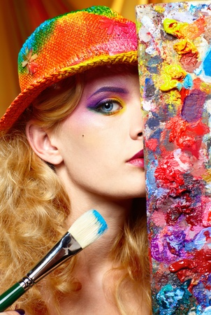 paint palette: close-up portrait of beautiful woman artist looking from behind of palette Stock Photo