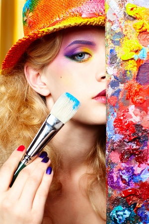 close-up portrait of beautiful woman artist looking from behind of palette Stock Photo
