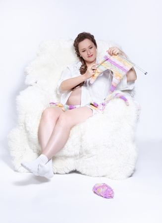 portrait of young beautiful pregnant woman in white furry arm-chair knitting baby's looses Stock Photo - 10280480