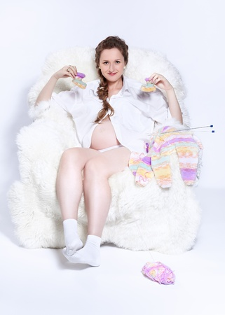 portrait of young beautiful pregnant woman in white furry arm-chair knitting babys looses photo