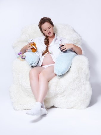 portrait of young beautiful pregnant woman in white furry arm-chair with two soft toy hares photo