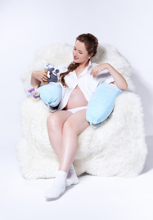 white socks: portrait of young beautiful pregnant woman in white furry arm-chair with two soft toy hares Stock Photo