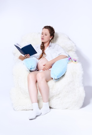 portrait of young beautiful pregnant woman in white furry arm-chair and reading book photo