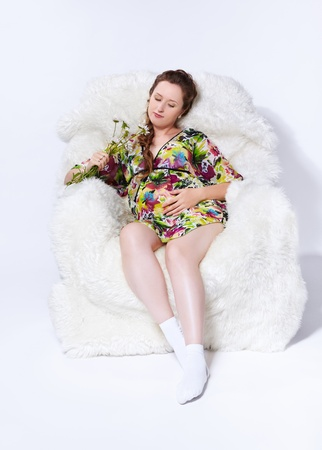portrait of young beautiful pregnant woman in white furry arm-chair with bunch of camomile flowers Stock Photo - 10280502