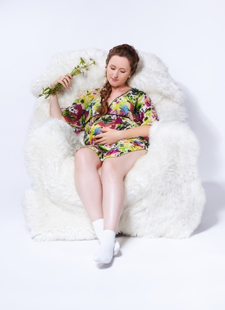 portrait of young beautiful pregnant woman in white furry arm-chair with bunch of camomile flowers photo