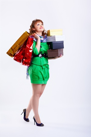 fancy box: full-length portrait of happy young shopaholic woman walking with shopping bags and boxes on gray