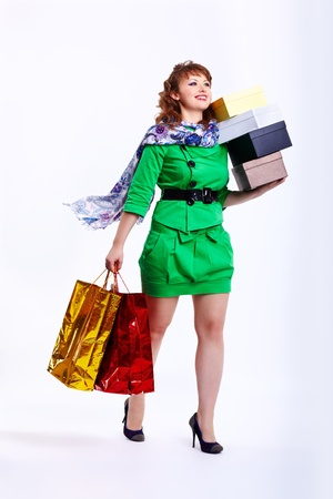 full-length portrait of happy young shopaholic woman walking with shopping bags and boxes on gray photo