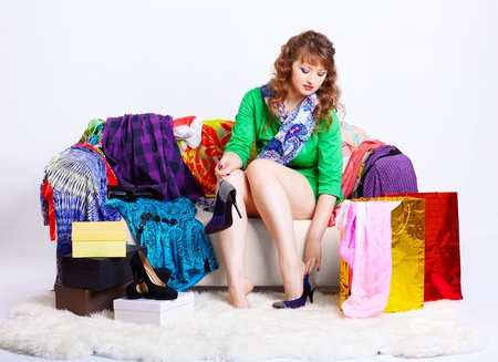 court shoes: full-length portrait of young shopaholic woman relaxing her tired legs on sofa among clothes, court shoes boxes and shopping bags Stock Photo