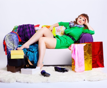 court shoes: full-length portrait of happy young shopaholic woman relaxing on sofa among clothes, court shoes boxes and shopping bags