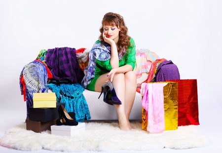 court shoes: full-length portrait of young shopaholic woman sitting on sofa among clothes, boxes and shopping bags and looking at new court shoes