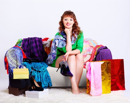 court shoes: full-length portrait of happy young shopaholic woman sitting on sofa among clothes, court shoes boxes and shopping bags