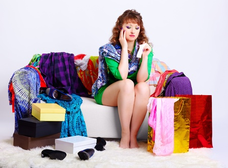 full-length portrait of young upset shopaholic woman with check in hand sitting on sofa with a lot of purchases around photo