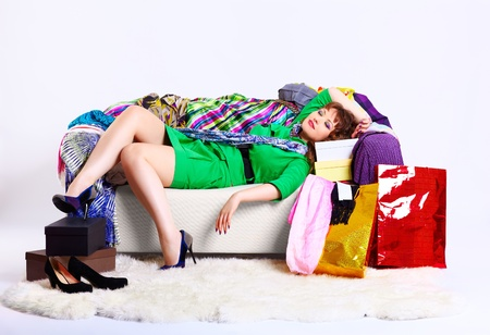 court shoes: full-length portrait of young shopaholic woman relaxing on sofa among clothes court shoes boxes and shopping bags Stock Photo