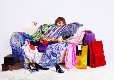shopaholics: full-length portrait of young shopaholic woman with credit cards hiding behind sofa with a lot of clothes and shopping bags