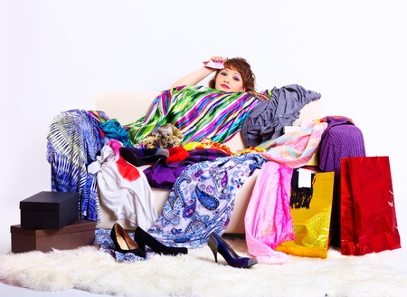full-length portrait of young shopaholic woman with credit cards sitting tired behind sofa with a lot of clothes and shopping bags photo