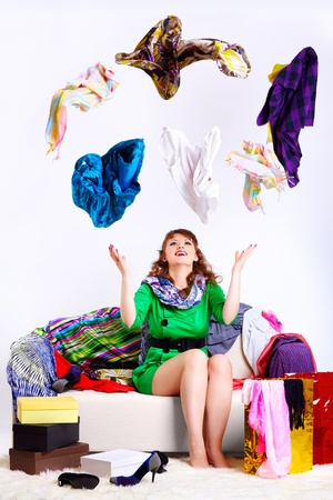 shopaholics: portrait of happy young shopaholic woman sittin on sofa wit purchases around and juggling clothes